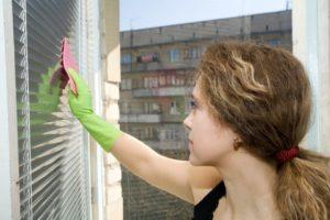 Młoda kobieta czyszcząca okno od zewnętrznej strony.