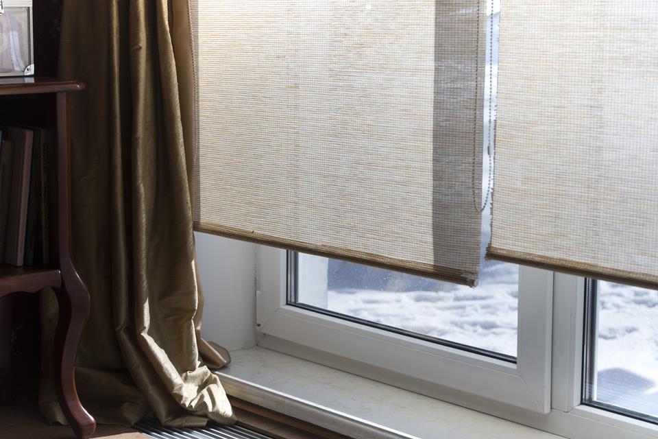 Rolety materiałowe na dużych oknach z długimi zasłonami.